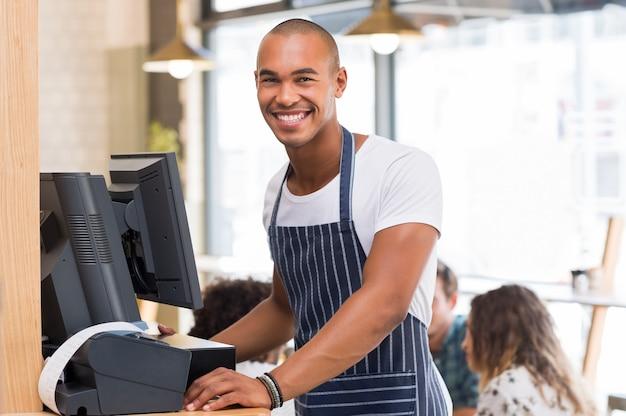 Portret van vrolijke jonge ober voorzijde kijken tijdens het afdrukken van factuur
