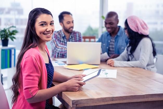 Portret van vrolijke jonge onderneemster die digitale tablet houden terwijl het zitten met collega's in bureau