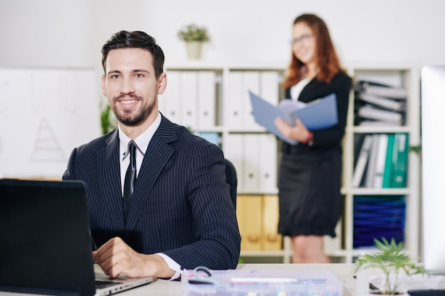 Portret van vrolijke jonge ondernemer die aan laptop bij zijn bureau werkt, zijn assistent die op achtergrond naar document zoekt
