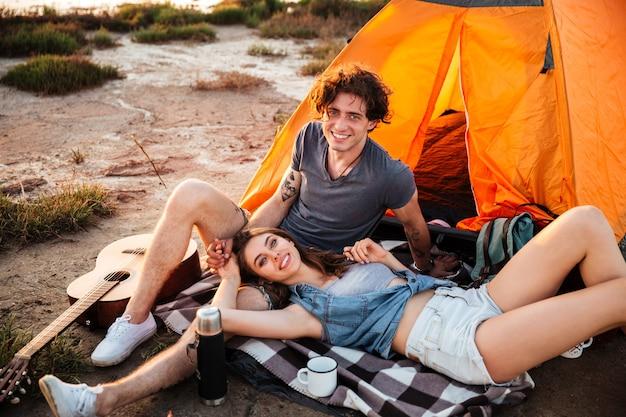 Portret van vrolijke jonge paar ontspannen in de tent van het kamp