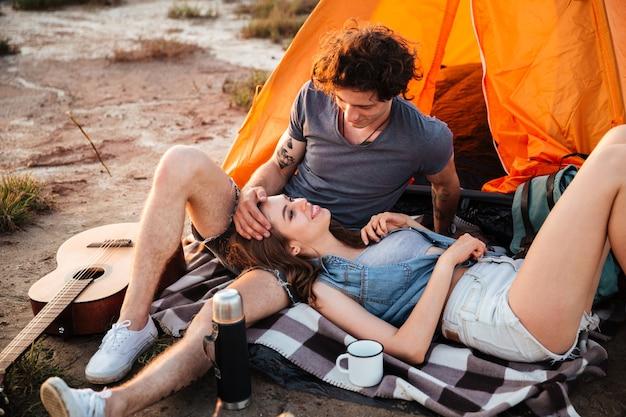 Portret van vrolijke jonge verliefde paar ontspannen in de tent van het kamp