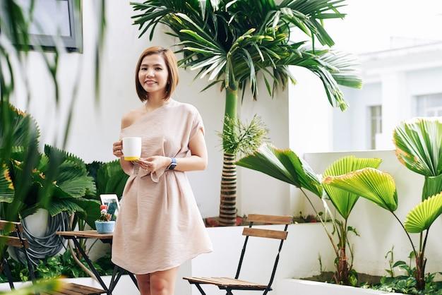 Portret van vrolijke jonge vietnamese vrouw poseren met mok hete heerlijke koffie aan café tafel