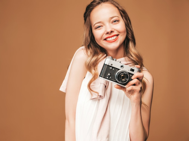 Portret van vrolijke jonge vrouw die foto met inspiratie nemen en witte kleding dragen. meisje dat retro camera houdt. model poseren