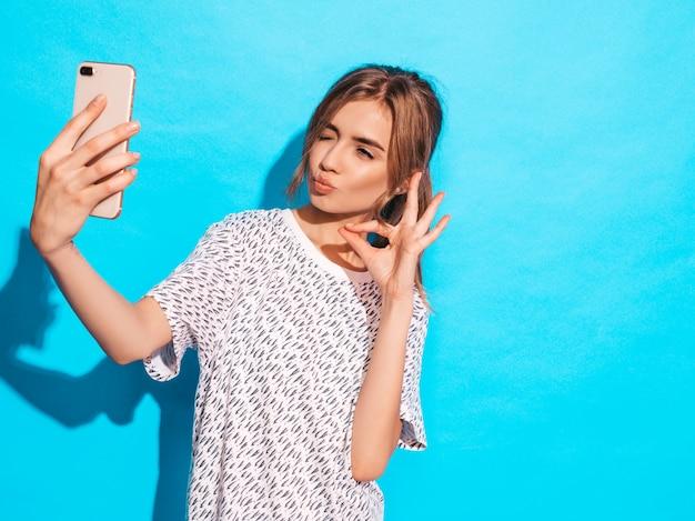 Portret van vrolijke jonge vrouw die foto nemen selfie. mooi meisje met smartphone camera. het glimlachen het model stellen dichtbij blauwe muur in studio. toont ok teken. knipoogt en maakt eendgezicht