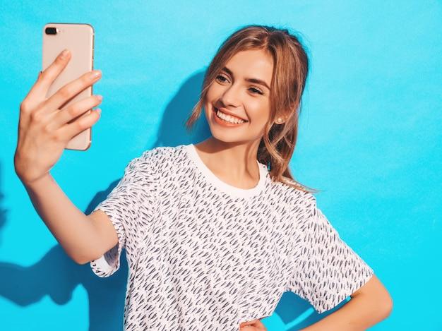 Portret van vrolijke jonge vrouw die foto nemen selfie. mooi meisje met smartphone camera. het glimlachen het model stellen dichtbij blauwe muur in studio