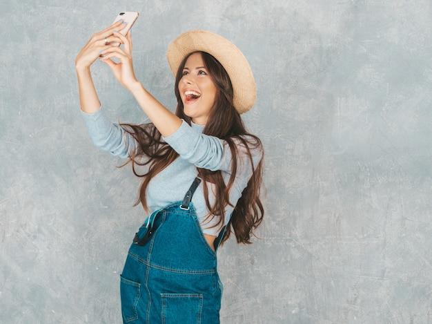 Portret van vrolijke jonge vrouw die foto selfie met inspiratie nemen en moderne kleren en hoed dragen.