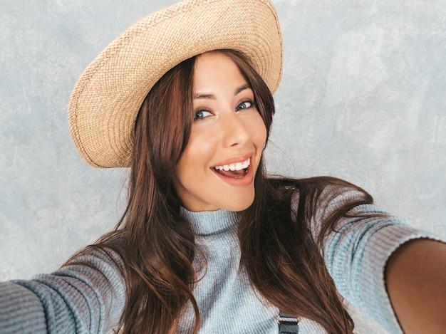Portret van vrolijke jonge vrouw die foto selfie nemen en moderne kleren en hoed dragen.