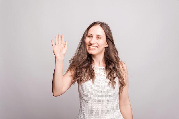 Portret van vrolijke jonge vrouw die hello-gebaar maakt