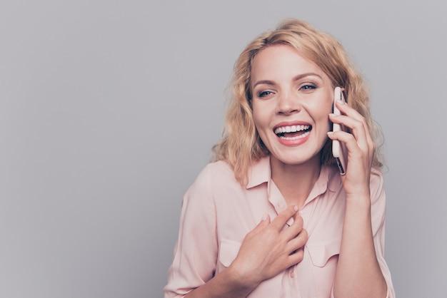 Portret van vrolijke jonge vrouw die op slimme telefoon spreekt die op grijs wordt geïsoleerd