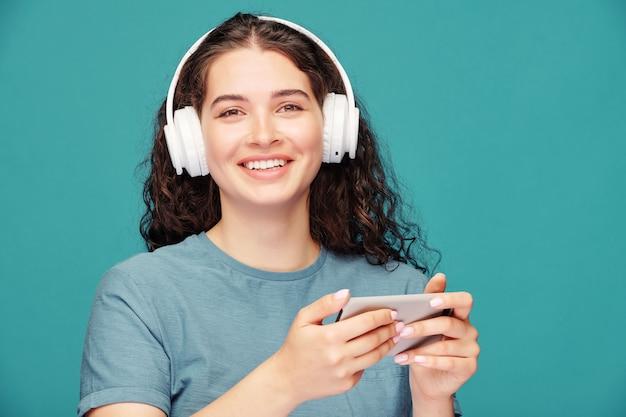 Portret van vrolijke jonge vrouw in draadloze koptelefoon kijken naar films op smartphone op blauw