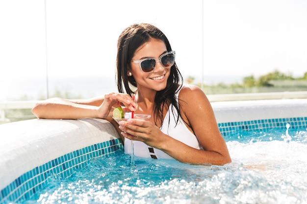 Portret van vrolijke jonge vrouw in witte zwembroek en zonnebril zitten in zwembad, en cocktail drinken buiten in kuuroord