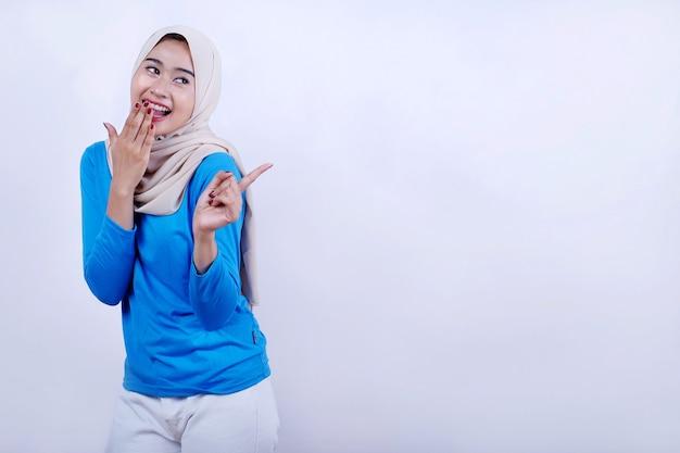Portret van vrolijke jonge vrouw met blauw t-shirt die hijab draagt, verrast voelt en met wijsvinger wijst