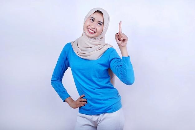 Portret van vrolijke jonge vrouw met blauw t-shirt die hijab draagt, zich gelukkig voelt en benadrukt