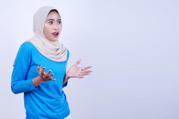 Portret van vrolijke jonge vrouw met blauw t-shirt die hijab draagt, zich geschokt, verbaasd en verrast voelt