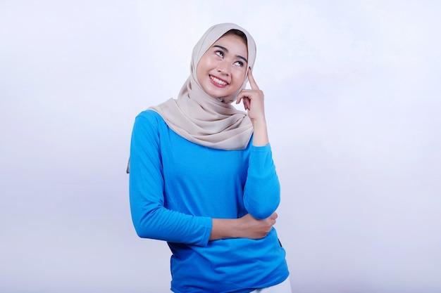 Portret van vrolijke jonge vrouw met blauwe t-shirt die hijab denkende uitdrukking draagt