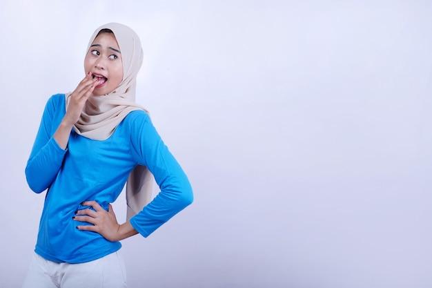 Portret van vrolijke jonge vrouw met blauwe t-shirt die hijab draagt, zich verrast en bang voelt