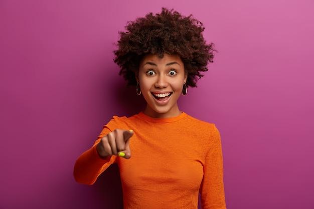 Portret van vrolijke jonge vrouw met donkere huid wijst met wijsvinger rechtuit, ziet iets verbazingwekkends, zegt hey you, draagt oranje trui, geïsoleerd over levendige paarse muur.