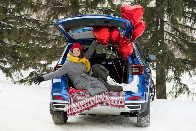 Portret van vrolijke jonge vrouw met hart vormen ballonnen, glimlachend alleen zittend op de kofferbak van de auto