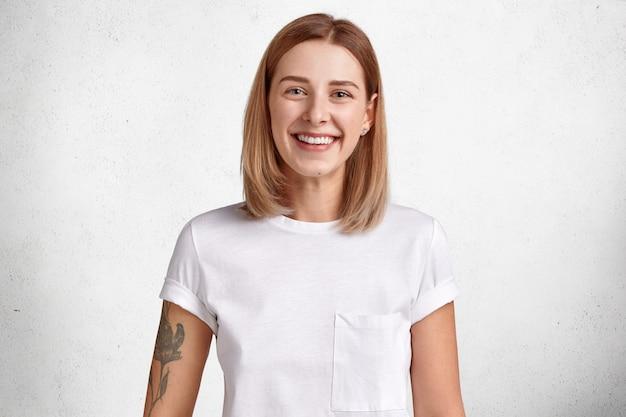 Portret van vrolijke jonge vrouw met kort haar, stralende glimlach, heeft tatoeage op arm, verheugt zich positief nieuws