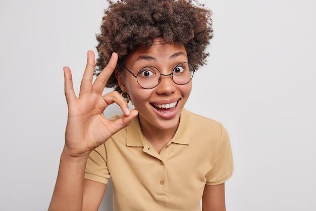 Portret van vrolijke jonge vrouw met krullend haar toont oké nulteken verzekert je dat alles in orde is, ziet er graag uit met een ronde bril, casual t-shirt poseert tegen een witte achtergrond. heel goed