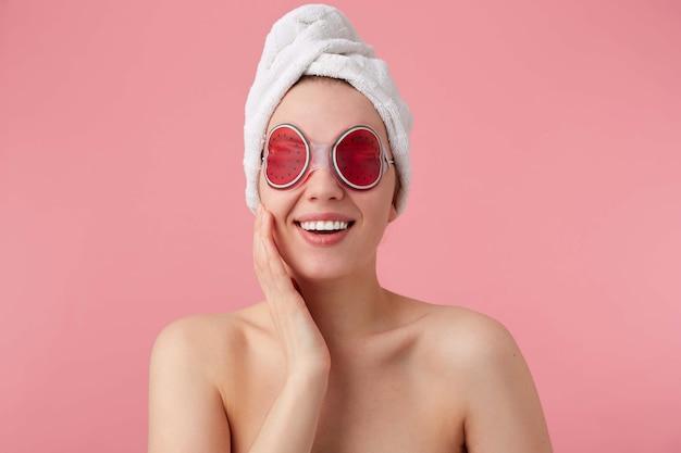 Portret van vrolijke jonge vrouw na kuuroord met een handdoek op haar hoofd, met masker voor ogen, breed glimlacht, voelt zo gelukkig, staat.