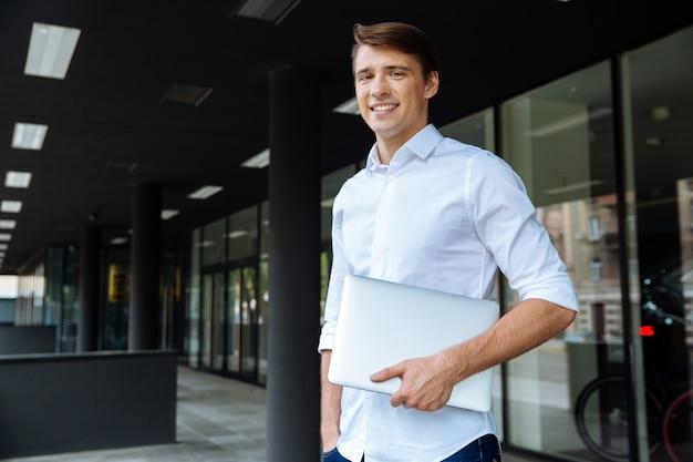 Portret van vrolijke jonge zakenman dichtbij zakencentrum