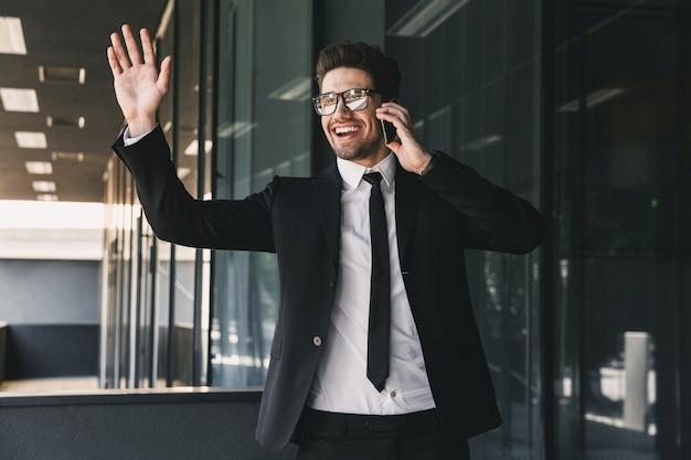 Portret van vrolijke jonge zakenman gekleed in formeel pak staande buiten glazen gebouw, en praten over de mobiele telefoon