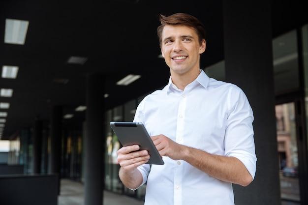 Portret van vrolijke jonge zakenman met behulp van smartphone en glimlachend in de buurt van zakencentrum