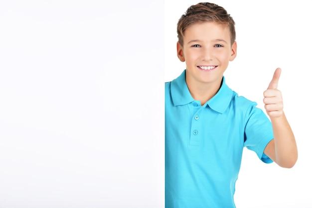 Portret van vrolijke jongen kijkt uit van het witte bordje met duim omhoog gebaar geïsoleerd op wit