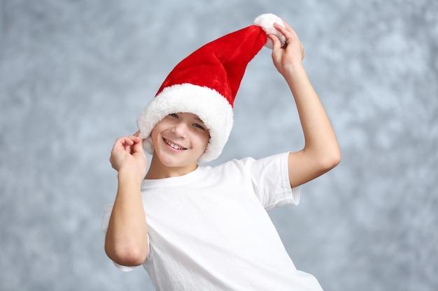 Portret van vrolijke jongen op grijze muur