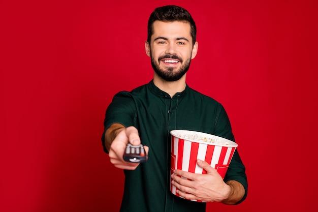 Portret van vrolijke kerel hebben vrije tijd tv kijken schakelaar afstandsbediening houden grote popcorndoos genieten van emotie draag goed uitziende outfit