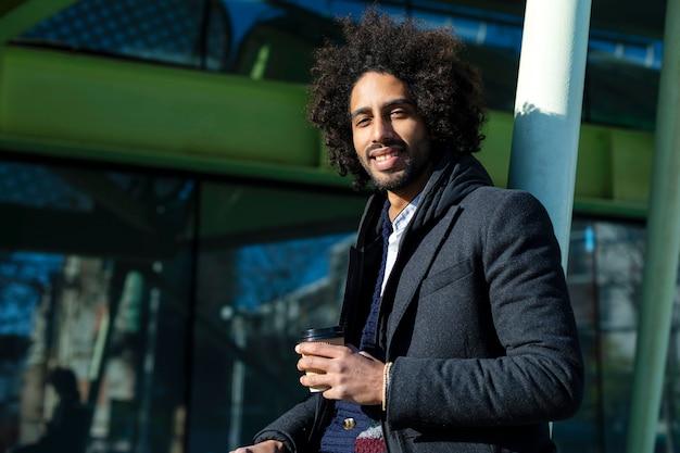 Portret van vrolijke knappe afro man in vrijetijdskleding poseren