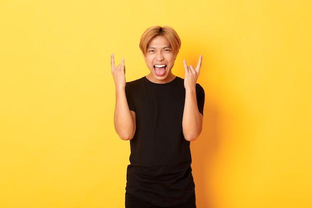 Portret van vrolijke knappe aziatische blonde kerel die pret heeft, rock-n-roll-gebaar toont en onbezorgd tong plakt, staande gele muur