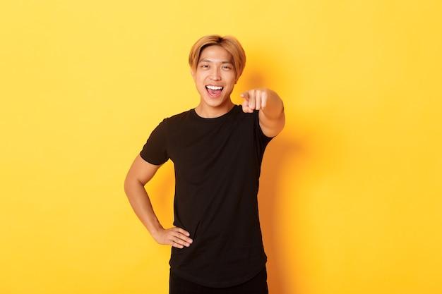 Portret van vrolijke knappe aziatische kerel met blond haar die jou kiezen, glimlachend en wijzende vinger, gefeliciteerd gebaar.