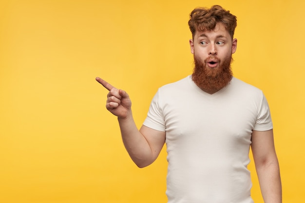 Portret van vrolijke knappe man met rood haar en baard, draagt een blanco t-shirt, wijzend met een vinger op kopie ruimte