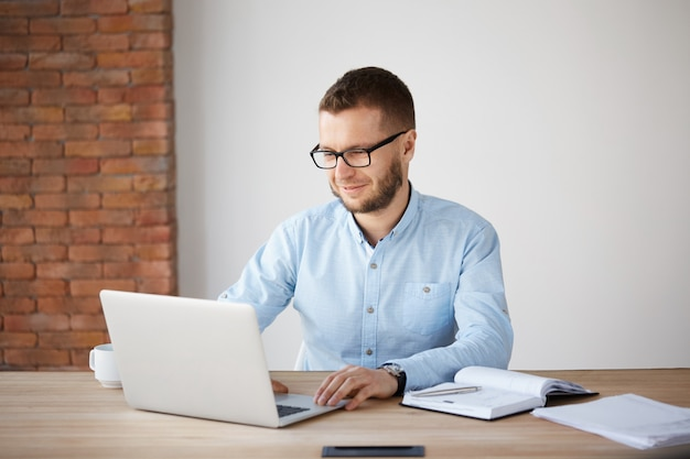 Portret van vrolijke knappe ongeschoren mannelijke bedrijfsleider in glazen en casual kleding zittend aan tafel in kantoor, zachtjes glimlachend, kijken naar laptop computermonitor, blij om favoriete werk te doen