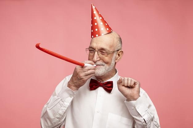 Portret van vrolijke knappe oudere gepensioneerde man met dikke grijze baard staande op roze studiomuur