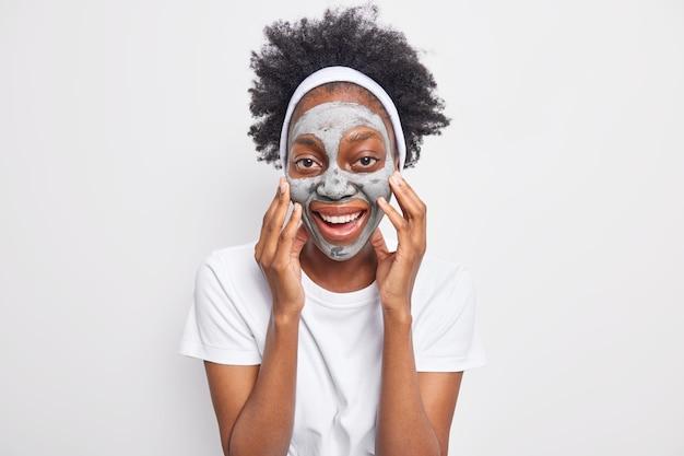 Portret van vrolijke krullende afro-amerikaanse vrouw raakt gezicht aan, past kleimasker toe voor huidbehandeling en verjonging lacht aangenaam