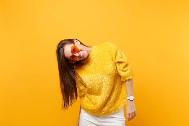 Portret van vrolijke lachende grappige jonge vrouw in bont trui, witte broek en hart oranje bril geïsoleerd op heldere gele achtergrond. mensen oprechte emoties, lifestyle concept. reclame gebied.