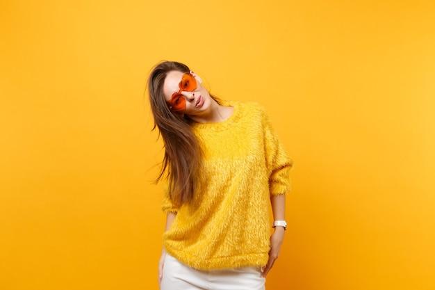 Portret van vrolijke lachende jonge vrouw in bont trui, witte broek en hart oranje bril geïsoleerd op heldere gele achtergrond. mensen oprechte emoties, lifestyle concept. reclame gebied.