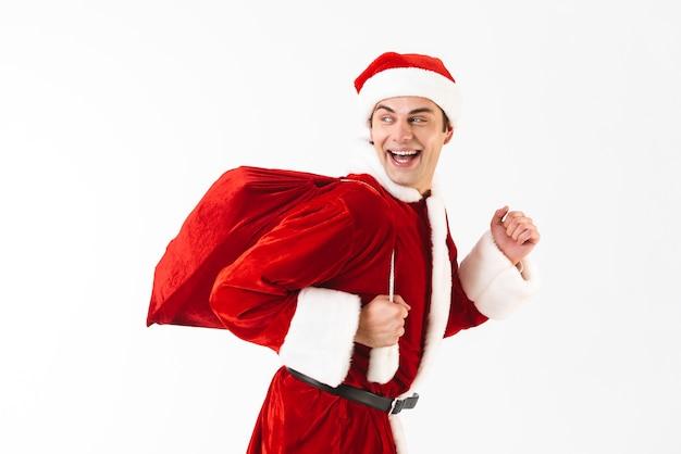 Portret van vrolijke man 30s in kerstman kostuum en rode hoed met cadeau zakje over schouder