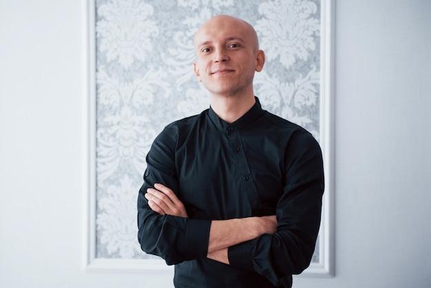 Portret van vrolijke man in de klassieke zwarte shirt met gekruiste armen