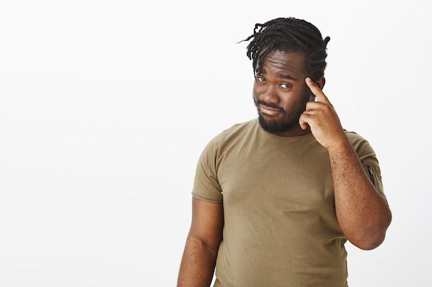 Portret van vrolijke man in een bruin t-shirt poseren tegen de witte muur