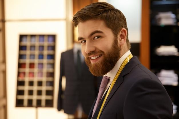 Portret van vrolijke man in pak in de garderobe
