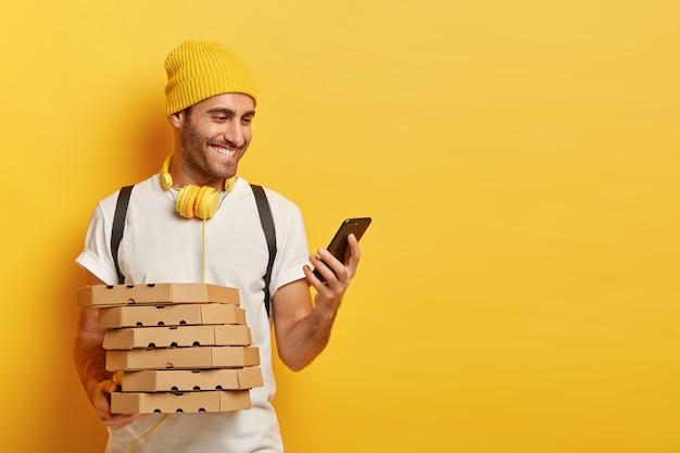 Portret van vrolijke mannelijke koerier controleert route naar huis van de klant op mobiele telefoon, houdt kartonnen dozen met pizza, terloops gekleed, luistert naar audio via koptelefoon