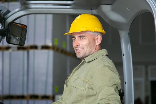 Portret van vrolijke mannelijke magazijnmedewerker in veiligheidshelm zittend op de vorkheftruckstoel, glimlachen, wegkijken