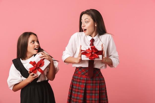 Portret van vrolijke meisjes in schooluniform die huidige dozen houden, terwijl status geïsoleerd over rode muur