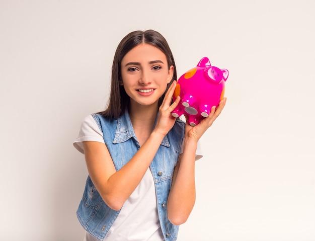 Portret van vrolijke meisjestiener die een roze varken houdt.