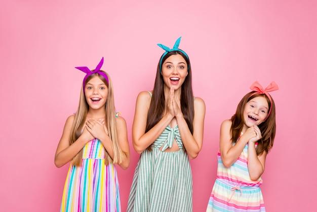 Portret van vrolijke mensen met hoofdbanden die wow omg gillen horen nieuws die kleurrijke kledingsrok dragen die over roze achtergrond wordt geïsoleerd