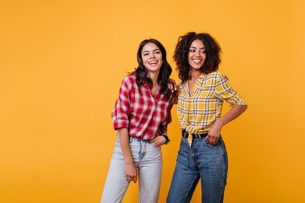 Portret van vrolijke modellen met krullen in geruite hemden. gebruinde meisjes hebben plezier.